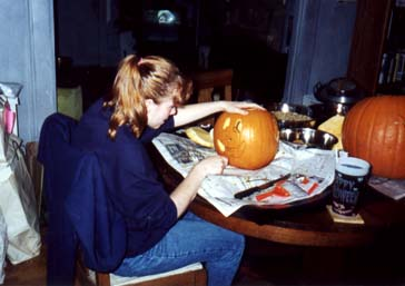 Anne carving a pumpkin