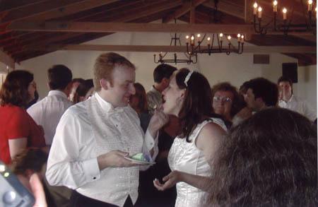 Brian and Meredith eating wedding cake