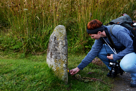 Anne at Well of the Dead grave marker at Culloden Battlefield