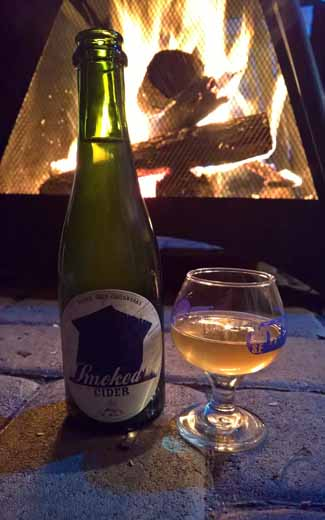 Tilted Shed Smoked cider in front of fire pit